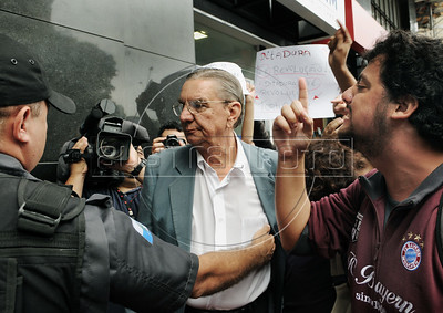 """Politic activists shout """"torturer"""" and """"murderer,"""" at a retired military man, center, arriving at a military club in downtownto celebrate the anniversary of 1964 military coup, Rio de Janeiro, Brazil, March 29, 2012. A club of retired military officers celebrates annualy lheld the Brazil's 1964 military coup, but faced protestors as members arrived for the event. (Austral Foto/Renzo Gostoli)"""