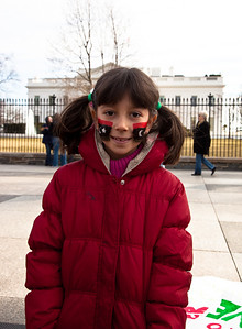 Seven year old Rana, wearing the 1951 first national flag of modern Libya on her cheeks, calls for the ouster of Libyan leader Moammar Gadhafi. Hundreds of demonstrators gathered in front of the White House calling on the United States to do more to help liberate Arab nations. The protestors stood in solidarity with pro-democracy movements taking place in Libya, Yemen, Bahrain, Iraq, Iran and the Sudan. In Washington DC on Saturday, February 26, 2011. (Photo by Jeff Malet)