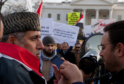 Several hundred demonstrators demanding that Egyptian President Hosni Mubarak vacate his office gathered outside the White House for a planned march to Capitol Hill in Washington DC on Friday, February 4, 2011. Mubarak has been head of government in Egypt for 30 years. In recent days, thousands of Egyptians have poured into the streets of several cities to call for a change in government. Here demonstrators communicate by cell phone to colleagues in Cairo. (Photo by Jeff Malet)