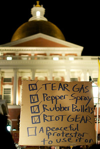 Nov. 15, 2011, Boston, MA – A sign held by a member of Occupy Boston outside the Massachusetts State House protests the allegedly violent tactics taken by police around the country to quell the movement.  In response to  the New York Police Department's crackdown of the Occupy Wall Street protest encampment about 15 hours prior, the members of Occupy Boston marched through the city to show solidarity with their fellow protestors all over the country. By Ryan Hutton