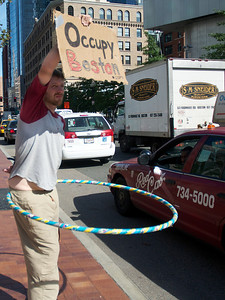 Oct. 7, 2011, Boston, MA - A member of the Occupy Boston protest holds up a sign to traffic on Atlantic Avenue while hula hooping. Photo by Ryan Hutton.