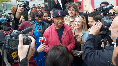 Nov. 15, 2011, Boston, MA – Members of the press and onlookers react after entrepreneur and co-founder of Def Jam Records Russell Simmons ditches his New York Yankees hat for a bystander's Boston Red Sox hat after speaking to about 100 people at the Occupy Boston protest in Dewey Square about better regulations of corporations and weeding out corporate-backed corruption in politics.  By Ryan Hutton