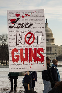 """Marie from Wichita KS says """"Love, Not Guns"""", in front of the U.S. Capitol. Approximately 100 residents from Newtown, Connecticut, the scene of a school massacre in which 20 children and six adults were killed last month, joined thousands of other anti gun violence activists on Saturday, January 26, 2013 in Washington D.C. in a march and rally on the National Mall in support of gun-control measures. (Photo by Jeff Malet)"""