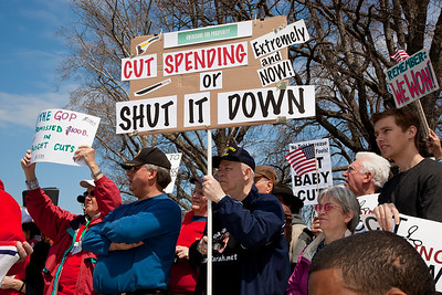 "Protestors demand ""Cut Spending Now"" near the steps of the Capitol building in Washington DC to urge lawmakers to reduce federal spending. The Tea Party style rally was organized by Americans for Prosperity, a conservative, free-market group. Party leaders on Capitol Hill are racing to overcome an impasse in budget talks that is threatening a partial shutdown of the United States government. In photo, protest sign says ""Cut Spending or Shut It Down"". April 6, 2011. (Photo by Jeff Malet)"