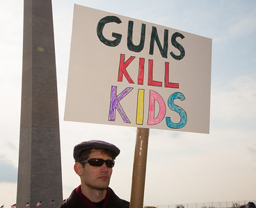 """""""GUNS KILL KIDS"""" reads this sign of protest. Wearing the green and white colors of Sandy Hook Elementary School where 26 children and adults were killed, 100 residents from Newtown, Connecticut joined thousands of other gun-control activists on Saturday, January 26, 2013 in Washington D.C. in a march down Constitution Ave. to a rally with speeches, musical performances and a poetry reading near the Washington Monument. (Photo by Jeff Malet)"""