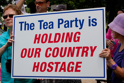 "Protestors declare ""The Tea Party is Holding Our Country Hostage"". Hundreds of progressive activists attended a rally held outside the Capitol Building in Washington DC on Thursday, July 28, 2011. The rally to ""Save the American Dream"" was organized to tell Democrats to stand strong against Republican debt ceiling proposals that cut Social Security, Medicare and Medicaid while keeping keep tax breaks for millionaires, billionaires and oil companies. Participants the AFL-CIO and major labor unions such as AFSCME, CWA, AFGE, Teamsters, and various progressive groups such as Move-On, Rebuild the Dream, Jobs with Justice, Gray-Panthers and Code-Pink."