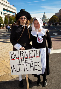"""Burneth the Witches"". Costumed protestors were common among the several hundred thousand who attended a ""Rally to Restore Sanity and/or Fear"" on the National Mall organized by Comedy Central talk show hosts Jon Stewart and Stephen Colbert  in Washington DC on Saturday, October 30, 2010. This couple dressed as pilgrims satirized Republican Senate Candidate Christine O'Donnell. It was also the day before Halloween. (Photo by Jeff Malet)"