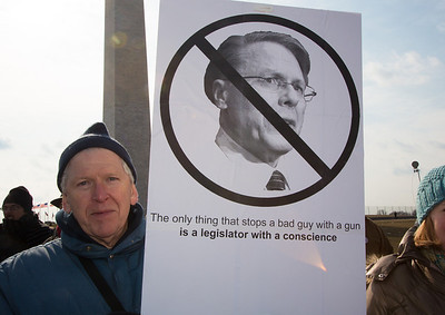 """""""The only thing that stops a bad guy with a gun is a legislator with a conscience"""" reads this protest sign paraphrasing the words of NRA Chief Executive Wayne LaPierre. Wearing the green and white colors of Sandy Hook Elementary School where 26 children and adults were killed, 100 residents from Newtown, Connecticut joined thousands of other gun-control activists on Saturday, January 26, 2013 in Washington D.C. in a march down Constitution Ave. to a rally with speeches, musical performances and a poetry reading near the Washington Monument. (Photo by Jeff Malet)"""