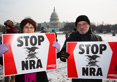 """Deborah and Rees from Riverdale MD say """"Stop the NRA"""" in front of the U.S. Capitol. Approximately 100 residents from Newtown, Connecticut, the scene of a school massacre in which 20 children and six adults were killed last month,  joined thousands of other anti gun violence activists on Saturday, January 26, 2013 in Washington D.C. in a march and rally on the National Mall in support of gun-control measures. (Photo by Jeff Malet)"""