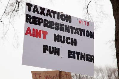 """The Tea Party Patriots political action group holds a Continuing Revolution Rally in Washington DC on March 31, 2011 to urge lawmakers to reduce federal spending. Party leaders on Capitol Hill are racing to overcome an impasse in budget talks that is threatening a partial shutdown of the United States government. In photo, protestor declares """"Taxation with representation ain't much fun either""""."""
