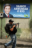 "A cop walks past an illegal campaign poster reading ""Let's Clean up Rio"" in a Rio de Janeiro slum promoting Marcelo Crivella for mayor. Crivella, an evangelical bishop, came in third place, behind Eduardo Paes and Fernando Gabeira.(Australfoto/Douglas Engle)"