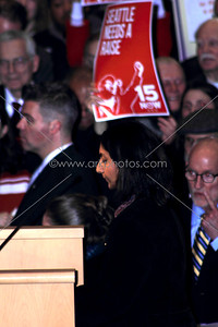 """New socialist Seattle City Council member Kshama Sawant speaking during inauguration 1/6/2014.Sign in back for campaign to raise the minimum wage to $15/hr, a major demand of her campaign. The sign is from a new organization started around the issue called """"15 Now"""".  www.15now.org"""