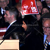 """New socialist Seattle City Council member Kshama Sawant speaking during inauguration 1/6/2014.Sign in back for campaign to raise the minimum wage to $15/hr, a major demand of her campaign. The sign is from a new organization started around the issue called """"15 Now"""".<br /> <br />  <a href=""""http://www.15now.org"""">http://www.15now.org</a>"""