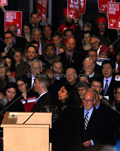 """New socialist Seattle City Council member Kshama Sawant speaking during inauguration 1/6/2014. Signs in back for campaign to raise the minimum wage to $15/hr, a major demand of her campaign. The signs are from a new organization started around the issue called """"15 Now"""".  www.15now.org"""