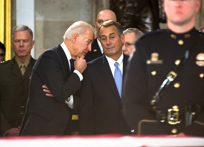 Vice President Joe Biden wispers to Speaker of the House John Boehner (R-OH) during ceremony for the late Senator Daniel Inouye. Members of the United States Capitol Police stand guard as Senator Inouye lies in state in the U.S. Capitol Rotunda in Washington D.C. on Thursday, Dec. 20, 2012. There, his colleagues and members of the public will pay their respects to the Senate's second-longest serving member. The Democrat from Hawaii was a Medal of Honor recipient for valor in World War II. He died Monday from respiratory ailments at age 88. Lying in state is an honor typically reserved for presidents, bestowed only 31 times since the 1800s. According to tradition, Inouye's casket sat underneath the Capitol dome, atop the Lincoln catafalque, the platform built in 1865 to support Abraham Lincoln's casket when that president's body lay in state.  (Photo by Jeff Malet)