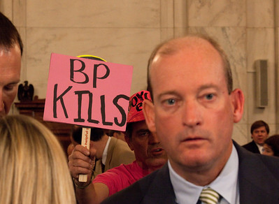 Protestor looks on as BP America's chairman, Lamar McKay waits to testify before the U.S. Senate Committee on Energy and Natural Resources investigating the recent oil spill in the Gulf of Mexico on Capitol Hill in Washington DC, Tuesday, May 11, 2010. Code Pink protestor holding sign. (Photo by Jeff Malet)