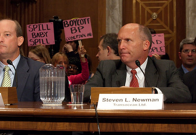 Code Pink protestors stand behind Transocean CEO Steven Newman during oil executives testimony before the U.S. Senate Committee on Environment and Public Works investigating the recent oil spill in the Gulf of Mexico on Capitol Hill in Washington DC, Tuesday, May 11, 2010 (Photo by Jeff Malet)