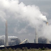 FILE - In this Wednesday, March 16, 2011 file photo, exhaust rises from smokestacks in front of piles of coal at NRG Energy's W.A. Parish Electric Generating Station in Thompsons, Texas. Risking an election-year backlash from Republicans, the Obama administration is proposing new air quality standards to lower the amount of soot that can be released into the air. The move by the Environmental Protection Agency on Friday, June 15, 2012 won immediate support from environmental groups and public health advocates, who said the EPA was protecting millions of Americans at risk of asthma attacks, lung cancer, heart disease and premature death. But congressional Republicans and industry officials called the rules overly strict and said they could hurt economic growth and cause job losses in areas where pollution levels are determined to be too high. (AP Photo/David J. Phillip)