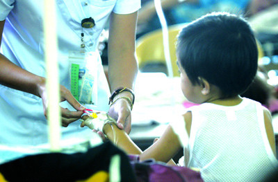 A nurse checks the  IV fluids from the arm of a dengue patient at the Pedia ward in CCMC.<br /> foto: Alex Badayos