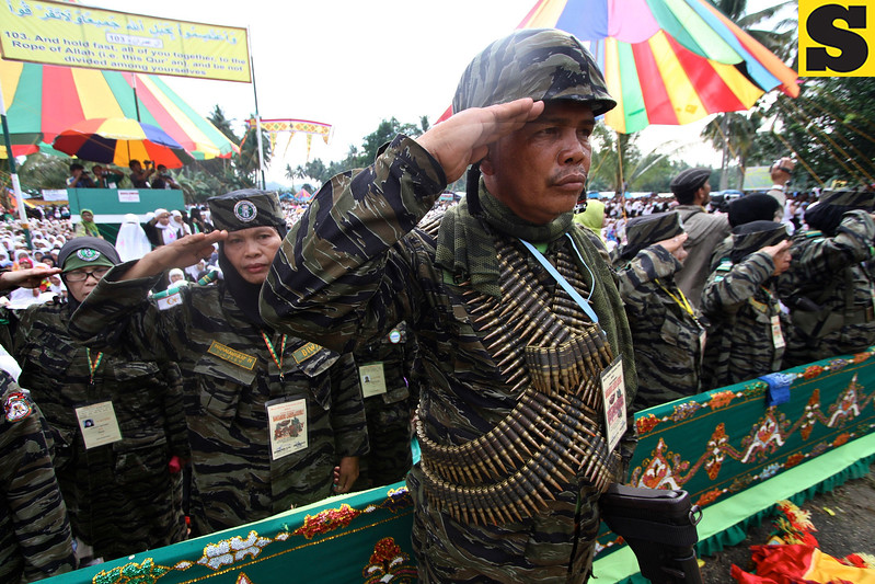 In this Saturday, July 7, 2012 photo, Muslim guerilla soldiers salute during a large gathering of followers and guerrillas belonging to the Moro Islamic Liberation Front at Camp Darapanan rebel headquarters in Sultan Kudarat municipality, Maguindanao province, southern Philippines. Rebel leaders organized the huge gathering to update and consult thousands of their rebels and followers on major developments in their years-long, Malaysian-brokered peace talks with the Philippine government. (AP Photo/Karlos Manlupig)