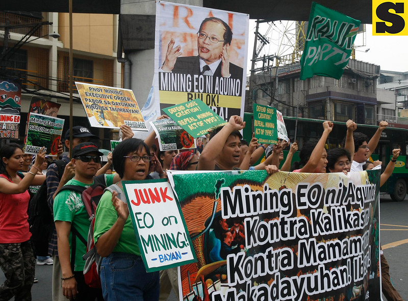 """Protesters march towards the Presidential Palace to protest the Executive Order on the new policy on mining in the country which President Benigno Aquino III signed over the weekend, in Manila, Philippines, Tuesday July 10, 2012. The protesters in their statement scored the new mining policy as tantamount to """"green washing to justify more profit-taking by foreign and large-scale miners."""" (AP Photo/Bullit Marquez)"""