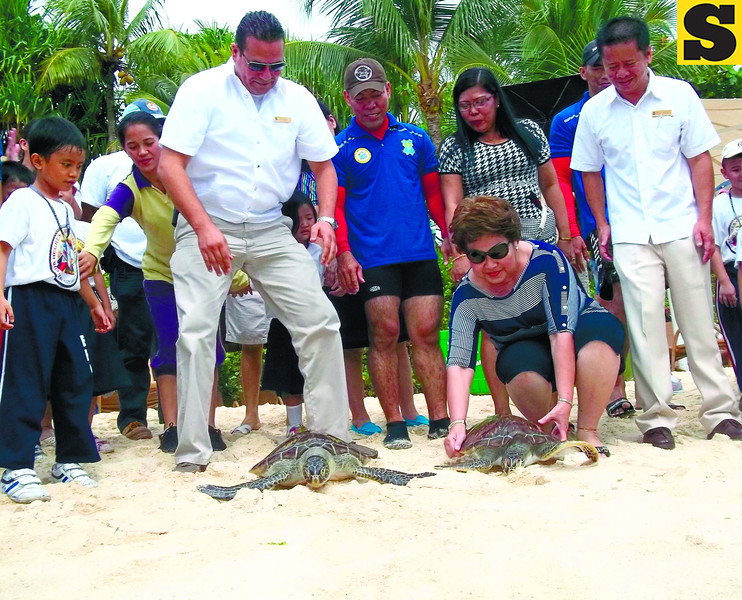 FREE.A male and a female Hawksbill turtles are set free near a marine sanctuary in Barangay Punta Engaño. Lapu-Lapu City Mayor Paz Radaza (second from right) leads the release of the endangered animals. With the mayor are officials of Task Force Kalikasan and Shangri-la's Mactan Island Resort.(Alan Tangcawan)