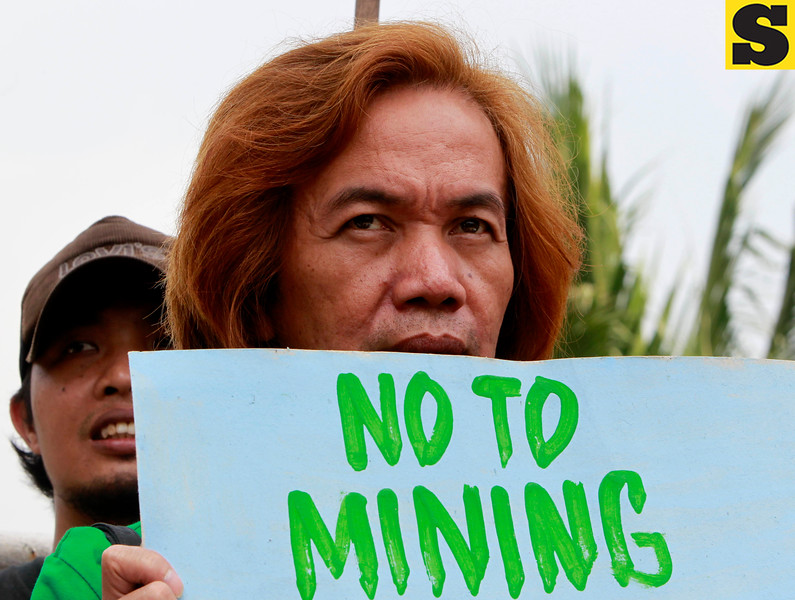 "Indigenous people display placards during a rally near the home of Philippine President Benigno Aquino III Wednesday July 11, 2012 at suburban Quezon city northeast of Manila, Philippines to protest the Executive Order he signed over the weekend on the new policy on mining in the country. The protesters alleged in their statement  the new mining policy continues to displace tribal communities and is tantamount to ""greenwashing to justify more profit-taking by foreign and large-scale miners."" (AP Photo/Bullit Marquez)"