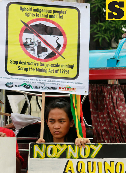"""Indigenous woman displays placards during a rally near the home of Philippine President Benigno Aquino III Wednesday July 11, 2012 at suburban Quezon city northeast of Manila, Philippines to protest the Executive Order he signed over the weekend on the new policy on mining in the country. The protesters alleged in their statement  the new mining policy continues to displace tribal communities and is tantamount to """"greenwashing to justify more profit-taking by foreign and large-scale miners."""" (AP Photo/Bullit Marquez)"""