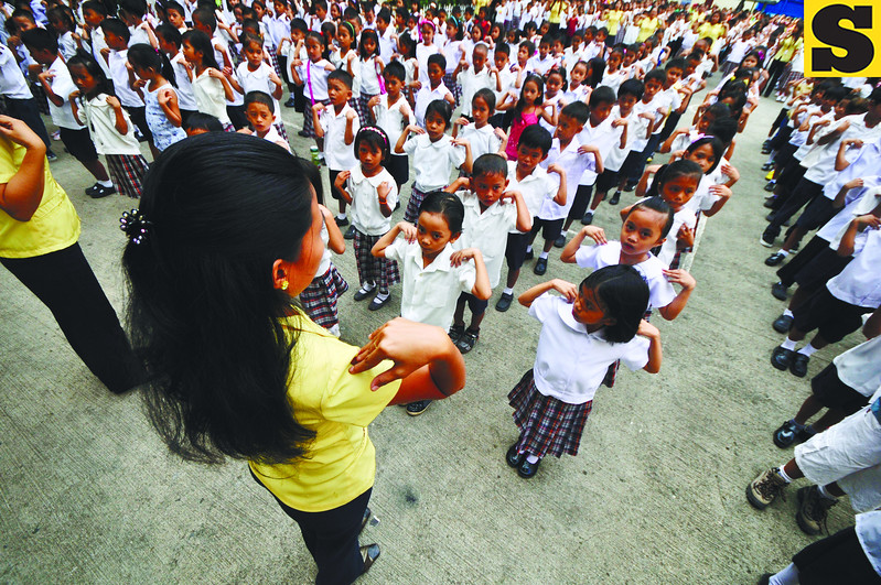 CEBU. Students at the Cebu City Central School prepare for their first day of class with a few body stretching exercises. This batch is young and unable to fully grasp how additional years in school as a result of the K-12 system will strain their families' budgets.  (Alex Badayos)