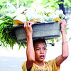 A boy sell vegetable carry in her head.<br /> foto: Alex Badayos