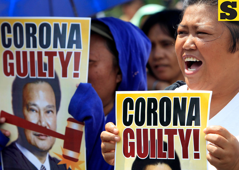 Protesters shout slogans as they display posters calling for a guilty verdict in the ongoing impeachment trial of Philippine Supreme Court Chief Justice Renato Corona Wednesday, May 23, 2012, in Manila, Philippines. Corona denied Tuesday before the senator-judges acting as impeachment court, he stole from the country's coffers and said he would open his bank accounts for inspection if the 188 lawmakers behind his impeachment do the same. (AP Photo/Bullit Marquez)