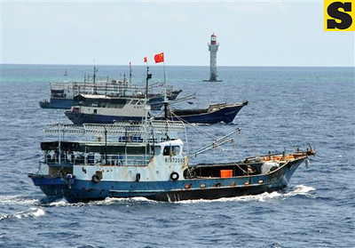 In this photo released by China's Xinhua, Chinese fishing vessels sail past a beacon of Zhubi Reef of the Spratly islands in South China Sea on Wednesday, July 18, 2012. A fleet of 30 fishing vessels from China's southernmost province of Hainan departed from Yongshu Reef in the Spratly on Tuesday night and arrived at Zhubi Reef Wednesday morning to fish and detect fishery resources in the area, Xinhua said. The Spratlys are a major cluster of potentially oil- and gas-rich islands and reefs long disputed by China, the Philippines, Taiwan, Malaysia, Vietnam and Brunei. (AP Photo/Xinhua, Wang Cunfu) NO SALES