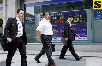 Office workers walk by the electric stock index display of a securities firm in Tokyo Wednesday, July 4, 2012. Asian stock markets were boosted Wednesday by hopes European central bankers will buoy economic growth with new stimulus measures. Japan's Nikkei 225 index rose 0.5 percent to 9,111.66. (AP Photo/Shizuo Kambayashi)