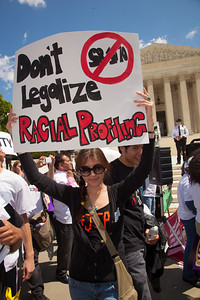 """Protestor holds sign that says """"Don't Legalize Racial Profiling"""". The U.S. Supreme Court heard arguments over a controversial Arizona law SB 1070 that requires police to check the immigration status of people they stop for any reason, as protestors for both sides rallied in front of the court steps in Washington D.C. on Wednesday, April 25, 2012. (Photo by Jeff Malet)"""