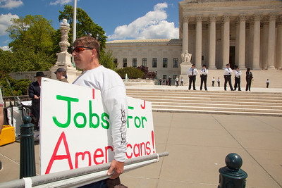 """Protestor holds sign that reads """"Jobs for Americans."""" The U.S. Supreme Court heard arguments over a controversial Arizona law that requires police to check the immigration status of people they stop for any reason, as protestors for both sides rallied in front of the court steps in Washington D.C. on Wednesday, April 25, 2012. (Photo by Jeff Malet)"""