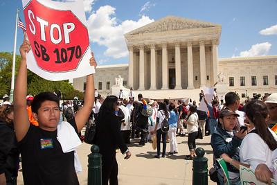 "Protestor holds sign against ""SB 1070"". The U.S. Supreme Court heard arguments over a controversial Arizona law SB 1070 that requires police to check the immigration status of people they stop for any reason, as protestors for both sides rallied in front of the court steps in Washington D.C. on Wednesday, April 25, 2012. (Photo by Jeff Malet)"