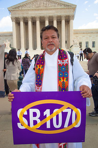 Rev. Hector Laporta, Pastor, Fourth Avenue United Methodist Church, Brooklyn, NY, stands in front of the U.S. Supreme Court. Members of the clergy marched against Arizona law SB 1070. The U.S. Supreme Court heard arguments over the controversial Arizona law that requires police to check the immigration status of people they stop for any reason, as protestors for both sides rallied in front of the court steps in Washington D.C. on Wednesday, April 25, 2012. (Photo by Jeff Malet)