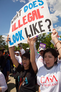 """Protestor holds sign that says """"What Does Illegal Look Like?"""". The U.S. Supreme Court heard arguments over a controversial Arizona law SB 1070 that requires police to check the immigration status of people they stop for any reason, as protestors for both sides rallied in front of the court steps in Washington D.C. on Wednesday, April 25, 2012. (Photo by Jeff Malet)"""