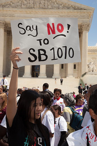 """Protestor holds sign against """"SB 1070"""". The U.S. Supreme Court heard arguments over a controversial Arizona law SB 1070 that requires police to check the immigration status of people they stop for any reason, as protestors for both sides rallied in front of the court steps in Washington D.C. on Wednesday, April 25, 2012. (Photo by Jeff Malet)"""