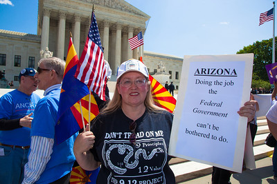 "Protestor holds sign that reads ""Arizona Doing the Job the Federal Government can't be bothered to do."" The U.S. Supreme Court heard arguments over a controversial Arizona law that requires police to check the immigration status of people they stop for any reason, as protestors for both sides rallied in front of the court steps in Washington D.C. on Wednesday, April 25, 2012. (Photo by Jeff Malet)"