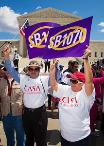 """Protestors holds signs against """"SB 1070"""". The U.S. Supreme Court heard arguments over a controversial Arizona law SB 1070 that requires police to check the immigration status of people they stop for any reason, as protestors for both sides rallied in front of the court steps in Washington D.C. on Wednesday, April 25, 2012. (Photo by Jeff Malet)"""