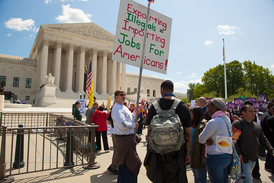 "Protestor holds sign that reads ""Exporting Illegals = Importing Jobs for Americans."" The U.S. Supreme Court heard arguments over a controversial Arizona law that requires police to check the immigration status of people they stop for any reason, as protestors for both sides rallied in front of the court steps in Washington D.C. on Wednesday, April 25, 2012. (Photo by Jeff Malet)"
