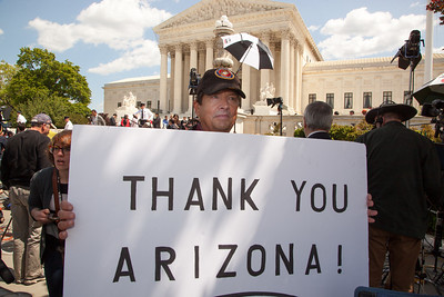 """Protestor holds sign that reads """"Thank You Arizona."""" The U.S. Supreme Court heard arguments over a controversial Arizona law that requires police to check the immigration status of people they stop for any reason, as protestors for both sides rallied in front of the court steps in Washington D.C. on Wednesday, April 25, 2012. (Photo by Jeff Malet)"""