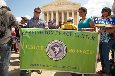 "Protestors from the Washington Peace Center hold sign against SB 1070 that reads ""No Justice, No Peace"". The U.S. Supreme Court heard arguments over a controversial Arizona law SB 1070 that requires police to check the immigration status of people they stop for any reason, as protestors for both sides rallied in front of the court steps in Washington D.C. on Wednesday, April 25, 2012. (Photo by Jeff Malet)"