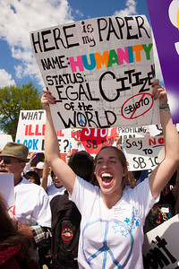 """Protestor holds sign that says """"Here is my paper name: Humanity - Status: Legal Citizen of the World"""". The U.S. Supreme Court heard arguments over a controversial Arizona law SB 1070 that requires police to check the immigration status of people they stop for any reason, as protestors for both sides rallied in front of the court steps in Washington D.C. on Wednesday, April 25, 2012. (Photo by Jeff Malet)"""