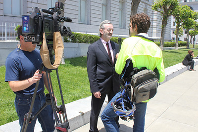 A reporter from KPFA conducts an interview with Kevin McCormack, a spokesperson for CPMC. To the left, a Channel 7 video reporter waits his turn to speak to Kevin.