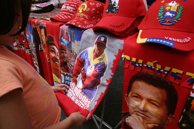 A girl looks at shirts of Venezuelan President Hugo Chavez in Caracas, Venezuela, Nov. 30, 2006. Chavez, first elected President in 1998 leads some opinion polls for the Dec. 3 2006 election with up to 60 percent of voter intentions. Chavez is a master of marketing and has achieved pop star status among the lower classes, who adore him.(AustralFoto/Douglas Engle)