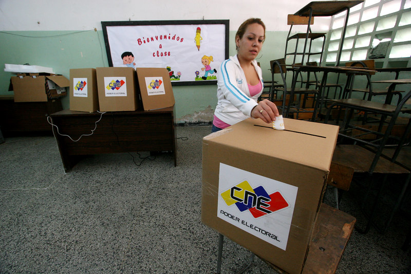 A woman votes at a voting station in the 23 de enero neighborhood in Caracas, Venezuela, Dec. 3 , 2006. The poor working class neighborhood is a stronghold of support for Venezuelan President Hugo Chavez. First elected President in 1998, Chavez leads some opinion polls for the election with up to 60 percent of voter intentions. Chavez is a master of marketing and has achieved pop star status among the lower classes, who adore him.(AustralFoto/Douglas Engle)