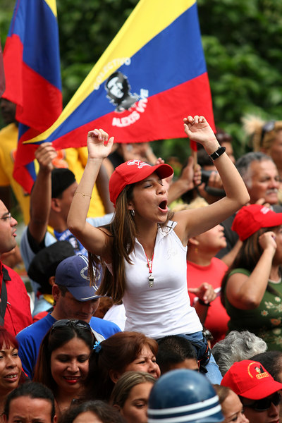 Supporters of Venezuelan President Hugo Chavez cheer upon his arrival to a voting station in the 23 de enero neighborhood in Caracas, Venezuela, Dec. 3 , 2006. The poor working class neighborhood is a stronghold of support for Venezuelan President Hugo Chavez. First elected President in 1998, Chavez leads some opinion polls for the election with up to 60 percent of voter intentions. Chavez is a master of marketing and has achieved pop star status among the lower classes, who adore him.(AustralFoto/Douglas Engle)