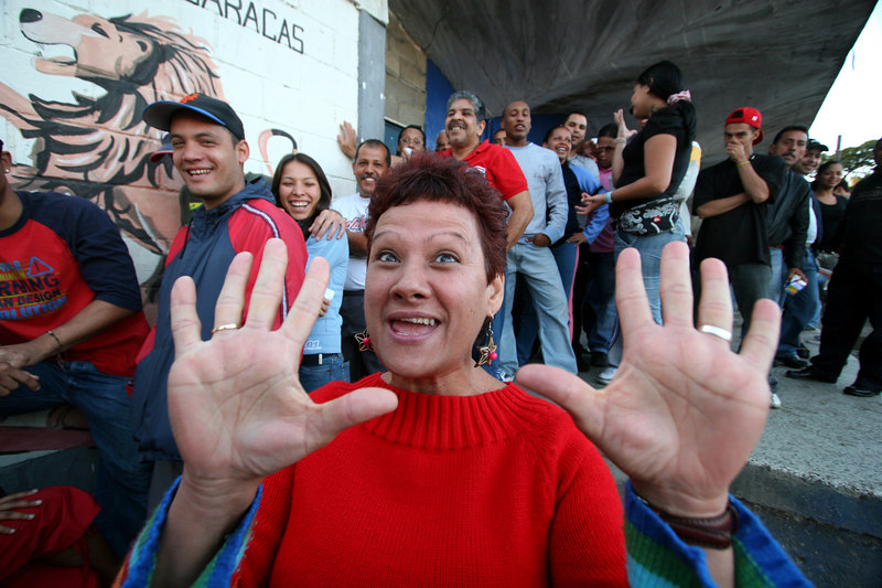 A woman show her 10 fingers, symbol of the Hugo Chavez campaign, near a voting station in the 23 de enero neighborhood in Caracas, Venezuela, Dec. 3 , 2006. The poor working class neighborhood is a stronghold of support for Venezuelan President Hugo Chavez. First elected President in 1998, Chavez leads some opinion polls for the election with up to 60 percent of voter intentions. Chavez is a master of marketing and has achieved pop star status among the lower classes, who adore him.(AustralFoto/Douglas Engle)